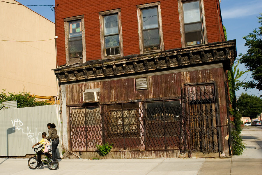 Kids Biking in Front of an Old Building in Red Hook